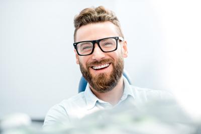 Hübscher Geschäftsmann mit großem Lächeln, das auf dem Zahnarztstuhl sitzt